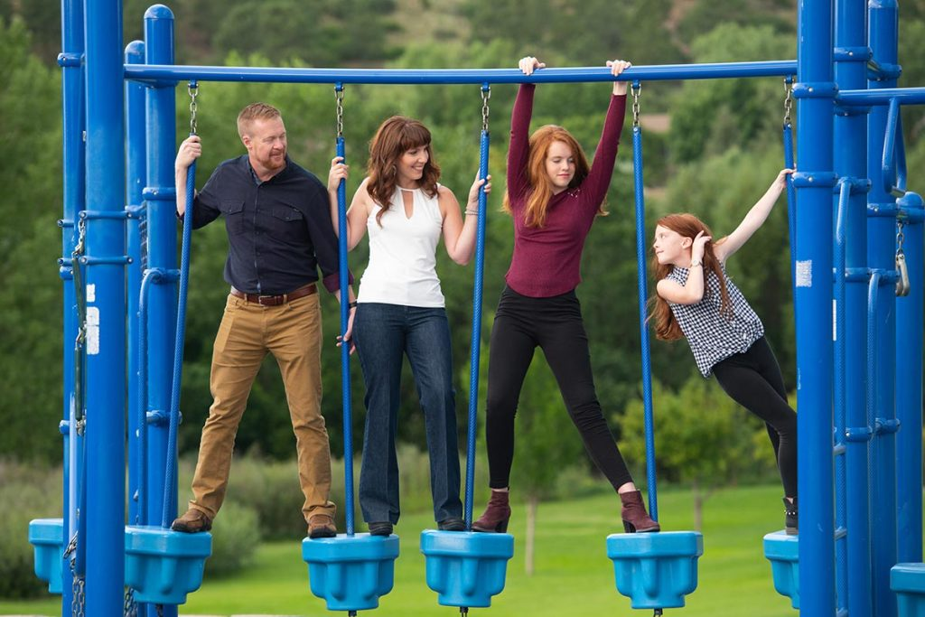 A photo of the Newbrough family on a set of swings