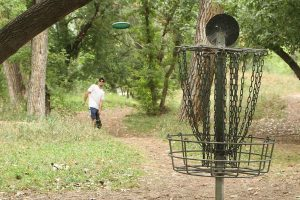 man tosses disc at disc golf basket