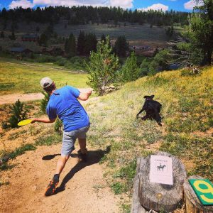 man tees off at a mountain disc golf course in Colorado while his dog enthusiastically goes after it.