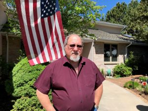 Gary Hall, a veteran, photographed in front of an American flag at his Pueblo home.