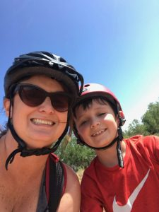 selfie of Kim and son with bike helmets on.