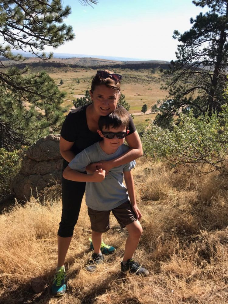 Kim with arms around son on top of a hill