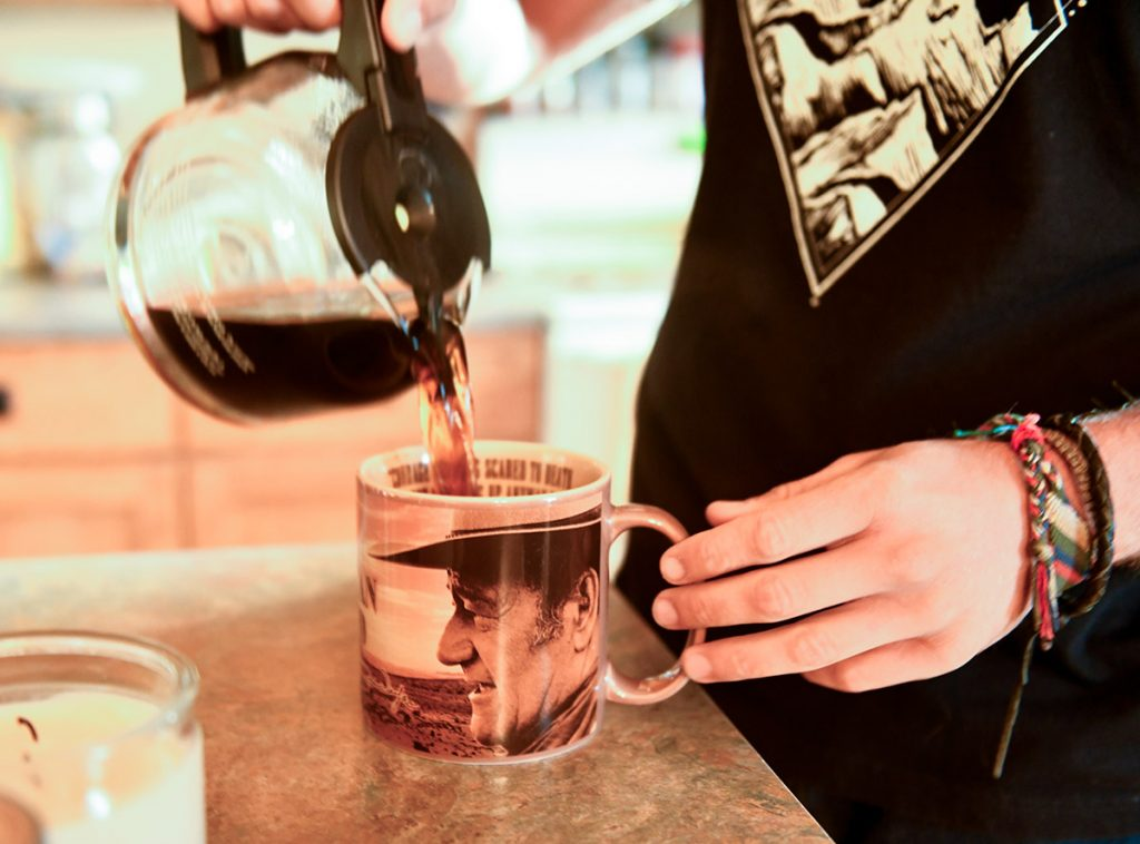 Nathan Kissack, a Wyoming rancher who had blood cancer, pours coffee into a John Wayne mug
