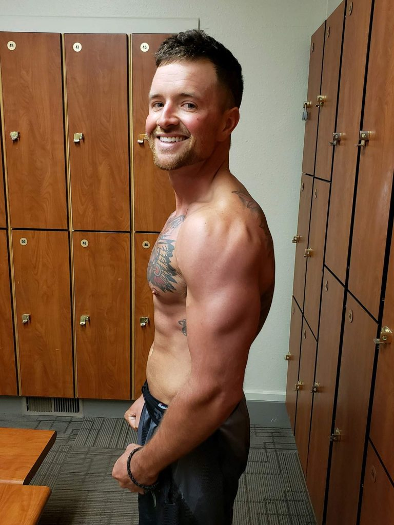 Nathan Kissack posing without a shirt after working out to get fit from cancer.
