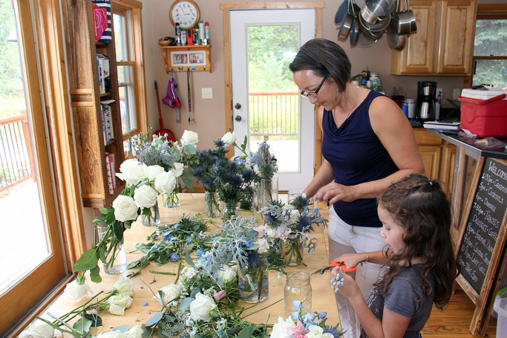 Alex and Jade Mathisen arrange flowers into glass vases at their kitchen table.