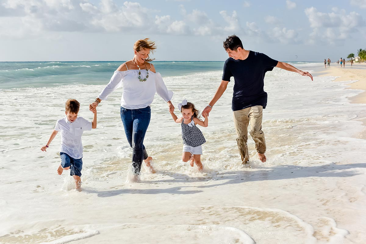 Parents running and holding hands with two kids at the beach, after David Procedure helped dad's heart.