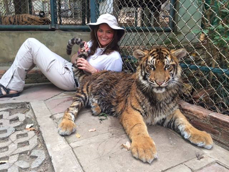 Marybeth Hoffman posing with a tiger during a trip to Thailand.