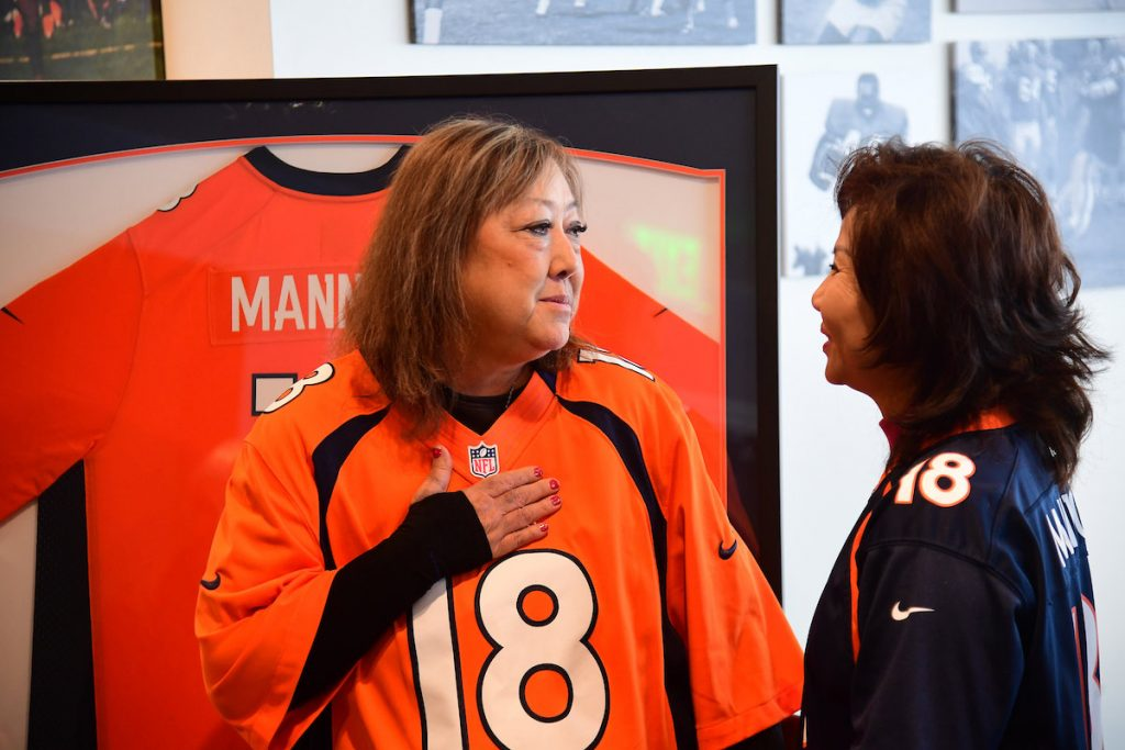 Linda Regis holds her hand over her chest as she wears a Denver Broncos jersey and talks to the mother of her lung donor.