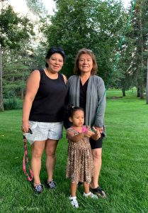 Three generations, mom, daughter and granddaughter, at a park.