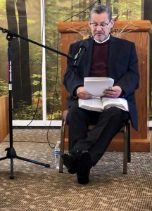 Michael sits on a chair in front of the church podium to give his last sermon.
