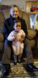 Grandfather smiles while holding his granddaughter between his legs.