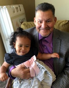 grandfather smiles holding smiling granddaughter on his lap.