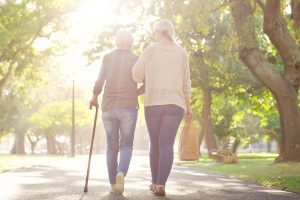 two women walk, one with a cane. fall prevention classes can help teach older people how to be safe.