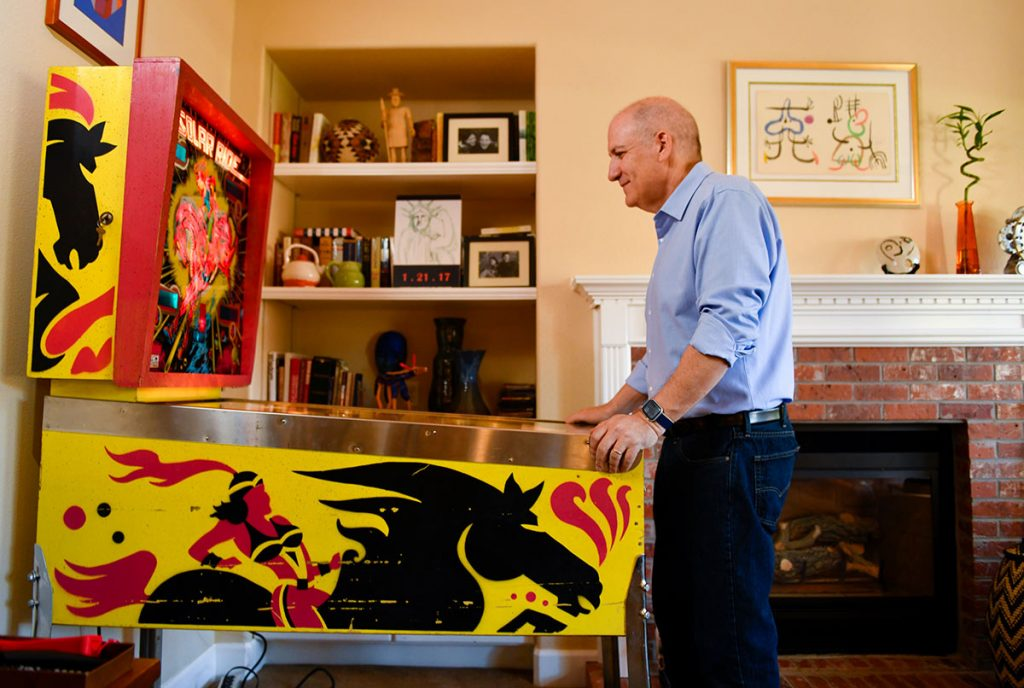 Jerry Oksner, who suffered a stroke in a hospital, plays pinball at home.