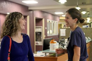 Two women, a former patient and nurse, laugh together in an ICU corridor. The patient returned to thank hospital staff for her care.
