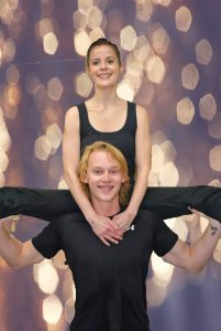 dancer with legs out on the shoulders of another dancer.