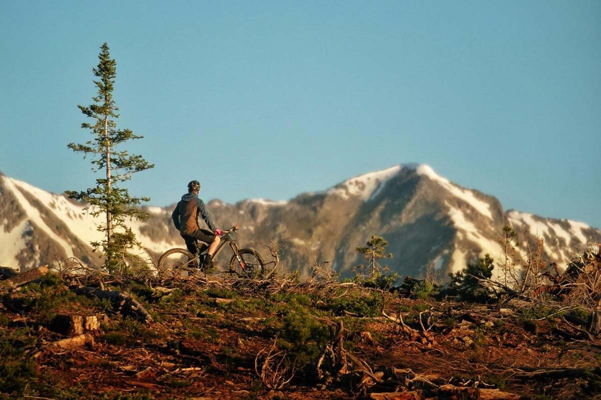 mountain biker resting on his bike looking at the large mountain range in the background after doctors repaired a devastating knee injury.