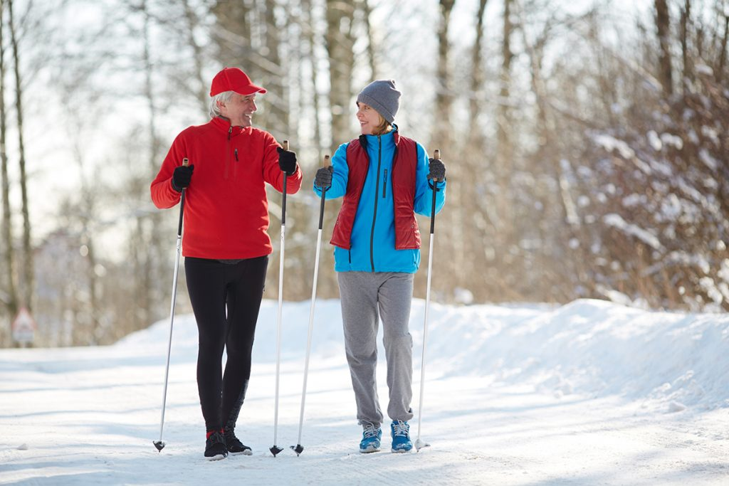 An older man and woman go for a walk on a snowy trail in this photo.