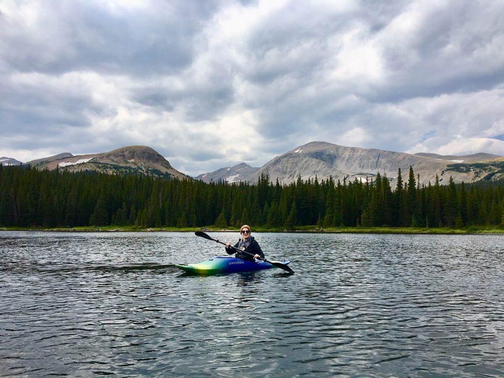 Lauren paddles a kayak on a mountain lake.