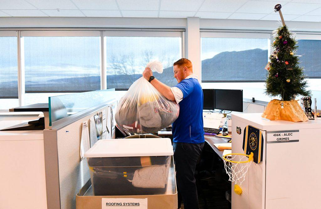 Frostbite survivor Alec Grimes sorts warm gear at his cubicle at Johns Manville in Littleton.