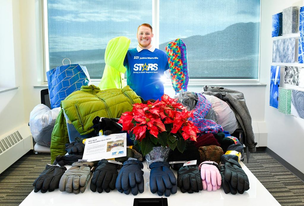 Frostbite survivor Alec Grimes poses with gloves, socks and coats he has gathered to give to homeless people.