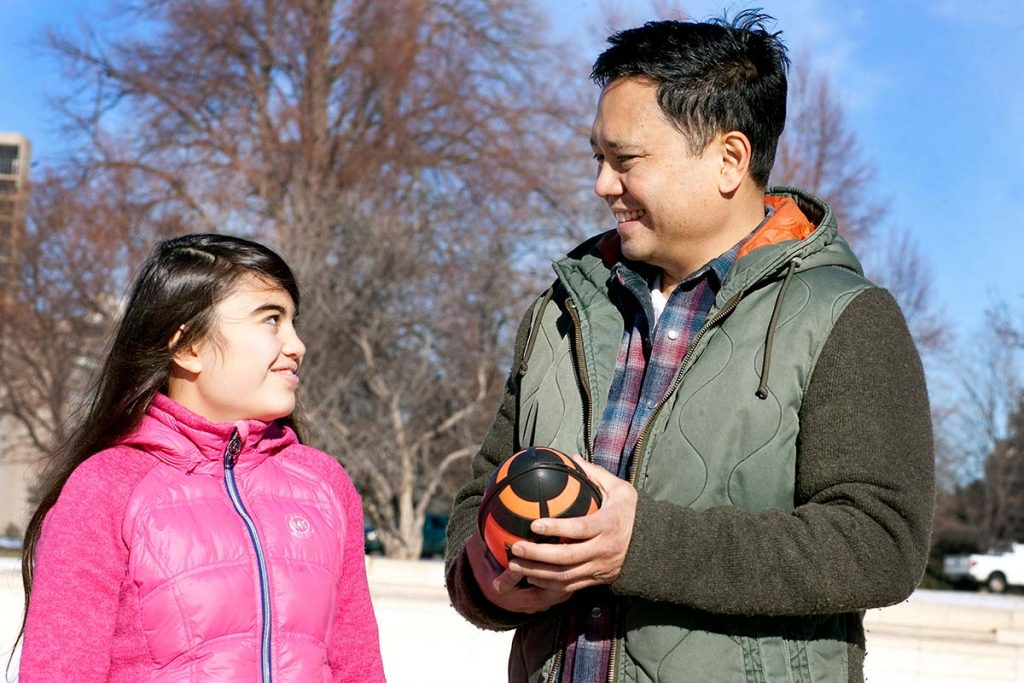 dad holds football while smiling at his teenage daughter.