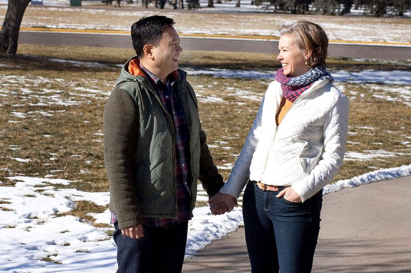 husband and wife smile at each other while hold hands in a park on a snowy day. They credit Victor being alive to the use of ECMO for acute respiratory distress syndrome that plagued Victor six years ago.