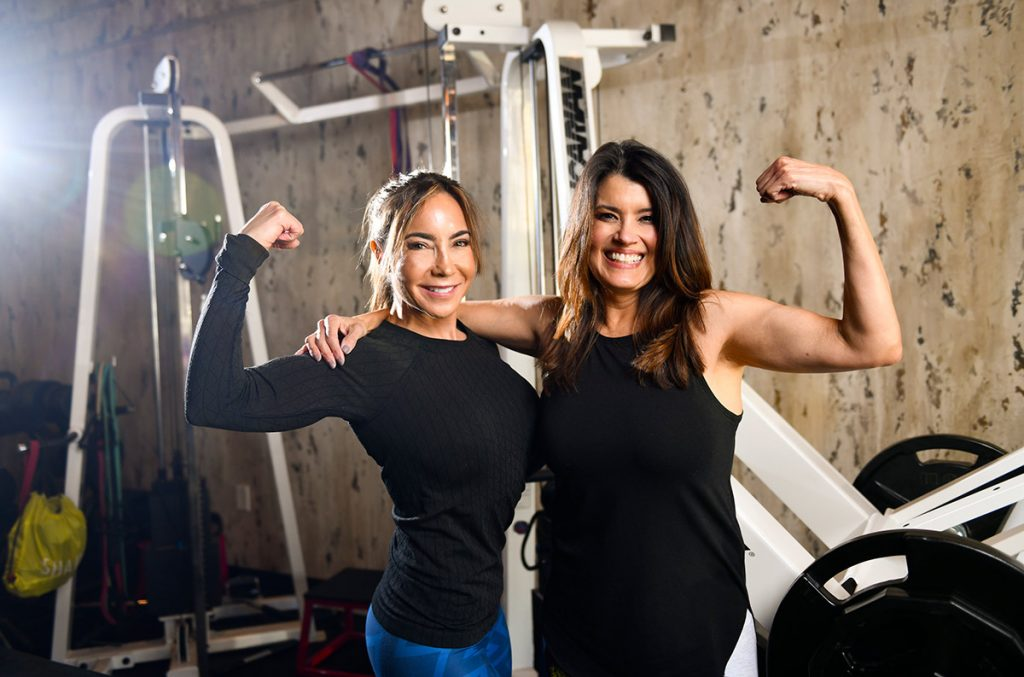 Lymphedema advocate Angela Maruez poses with her trainer, Carla Sanchez. Both are flexing their muscles.