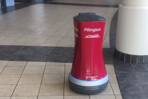 A red, cylindical robot on wheels moves through a hallway to deliver medications