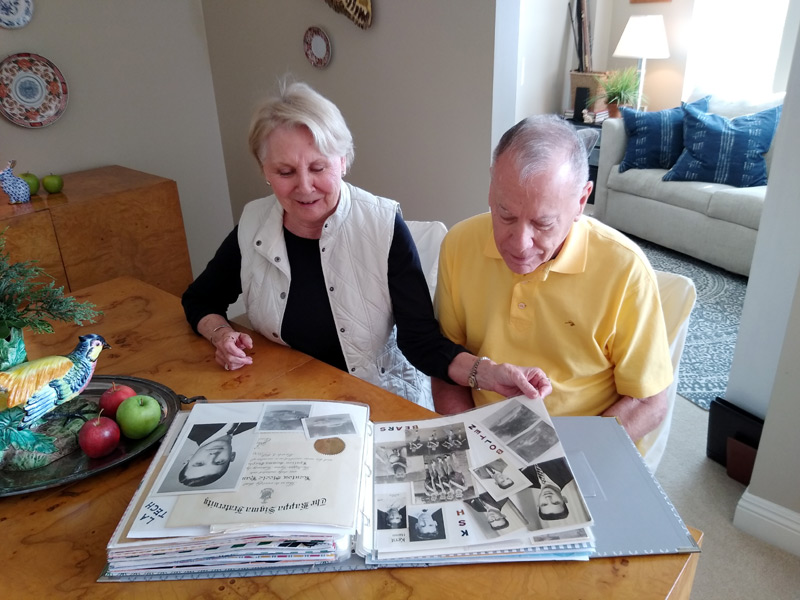 couple looks at a scrap book that helps the husband, who is living with dementia, remember things.