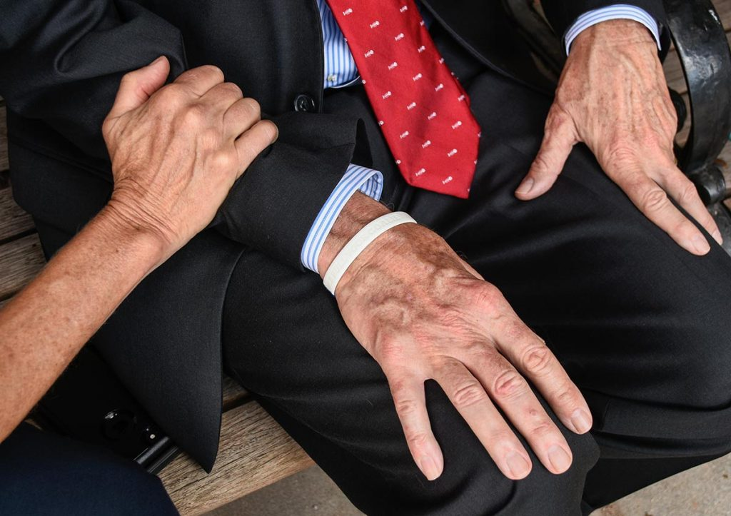 The photo shows the hands of Chester and Mimi wheeler. Inspired by extraordinary kindness of a stranger and caregivers helped Chester recover from a traumatic cycling accident.