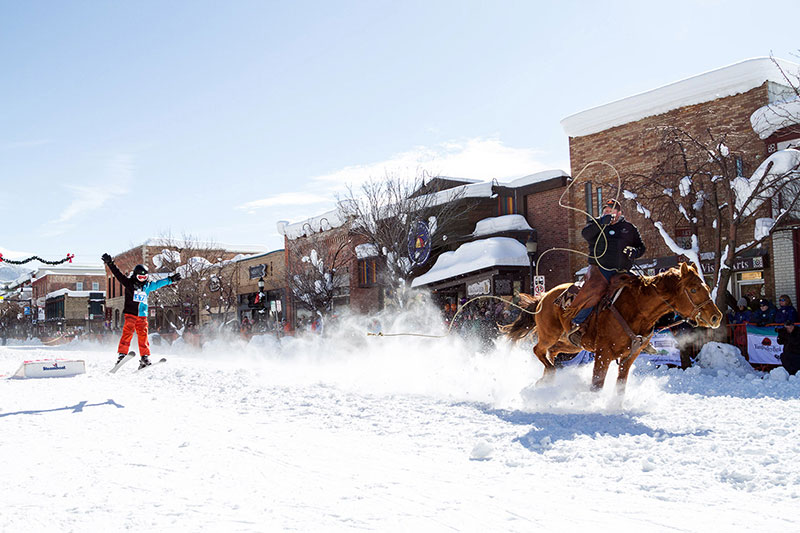 A horse pulls a skier holding a rope down a snow-covered street.
