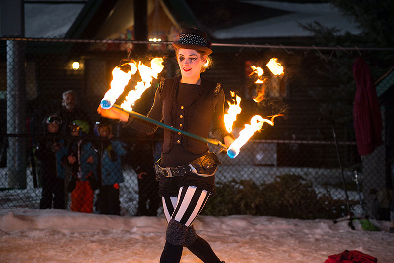 A woman twirls a fiery baton in this photo.