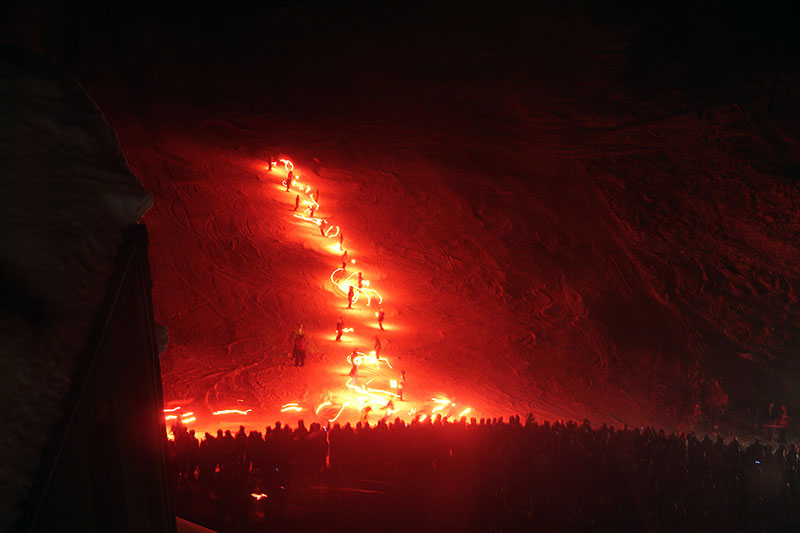 Skiers holding flares ski down a mountain at night in this photo.
