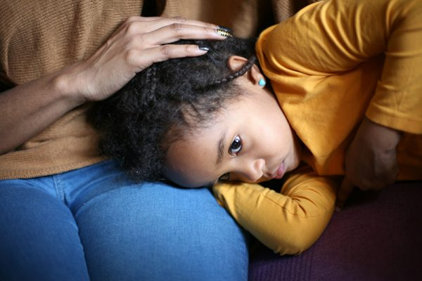 A sick child on her mom's lap. Flu season in 2020 has been especially hard on children.
