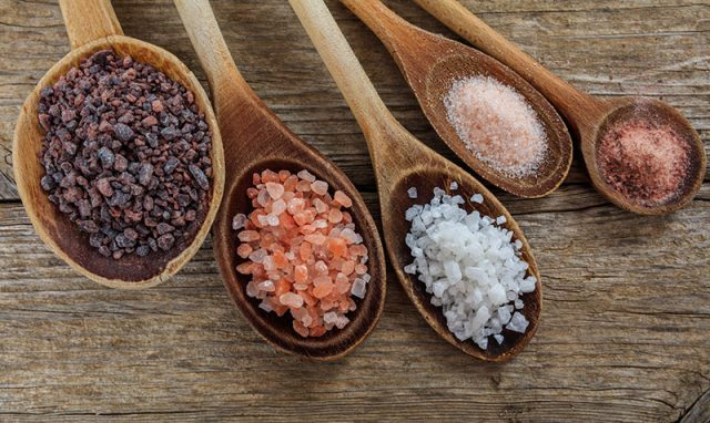 This photo shows cooking spoons with different colors of salt crystals to help explain what is salt.