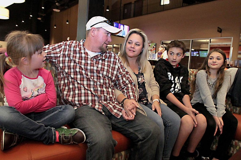 The alexander family sit on a bench for family bowling night, being able to return to the fun event months after Keith, the father, was diagnosed with colon cancer.