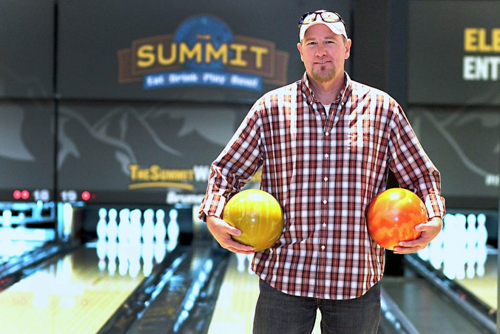 keith stands holding two bowling balls in front of the bowling lane.