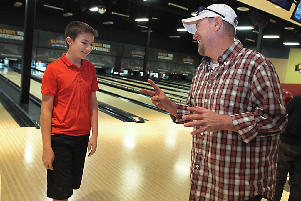 Keith talks with his son at the bowling alley.