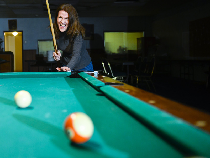 women laughs, pool stick in her hand, as ball rolls down the table.