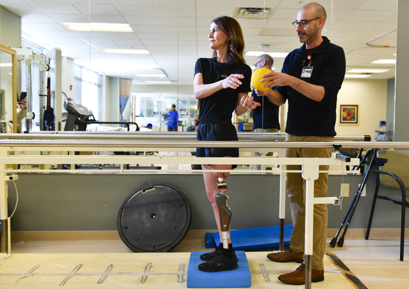 physical therapist works with woman after her osseointegration surgery.