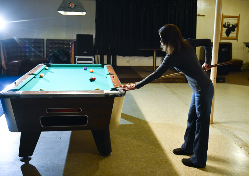 woman gets ready to take pool table shot.