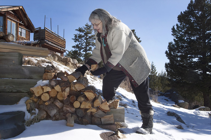 woman stacks firewood on a hill outside her home.