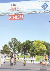 The Malone family crosses the finish line of a bike race in this photo.