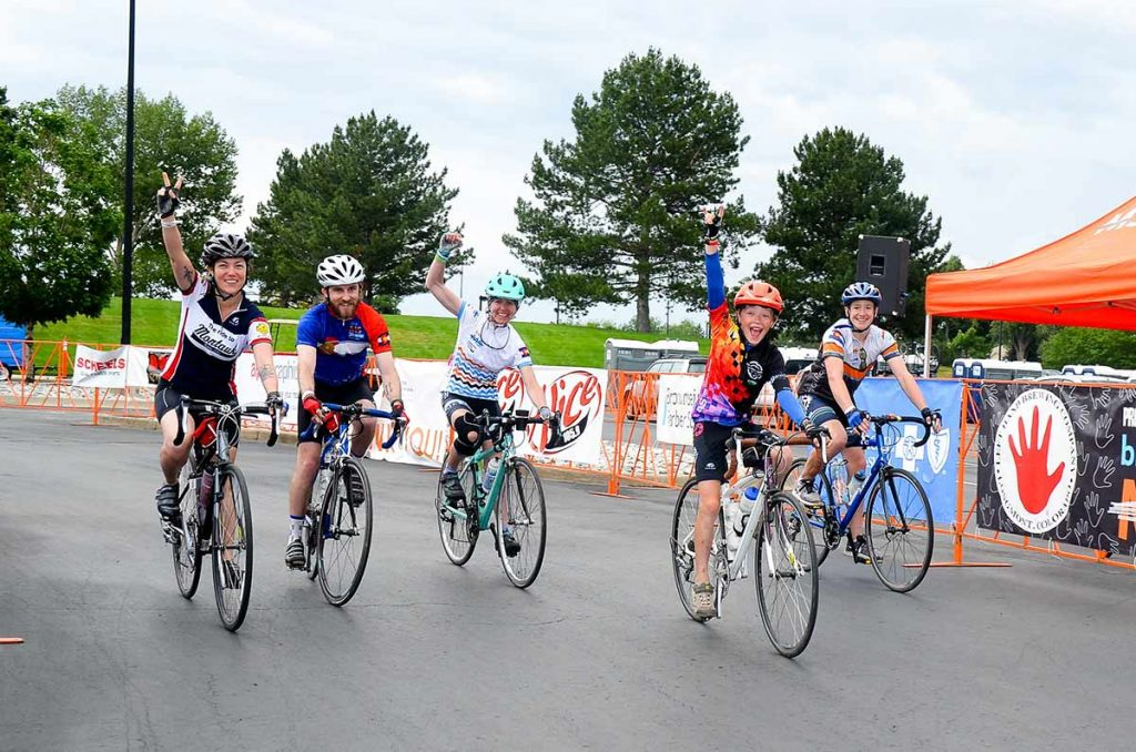 Lane Malone, her son, Sal, and other riders cross the finish lane of the Bike MS ride in this photo.