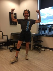 Lane Malone raises her arms with excitement after being fitted for an ankle-foot orthosis in this phohto.