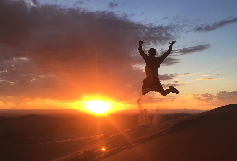 A man jumps off Star Dune at sunset.