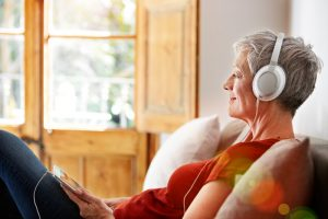 Women with headphones on because music should be on your wellness toolbox list.