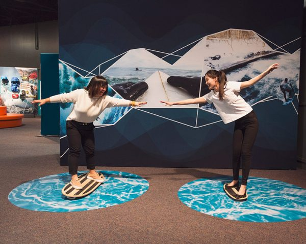 young women enjoy an exhibit on extreme sports at the Denver Museum of Nature and Science during free days at denver cultural institutions.