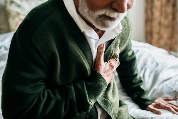 older adult holding his heart